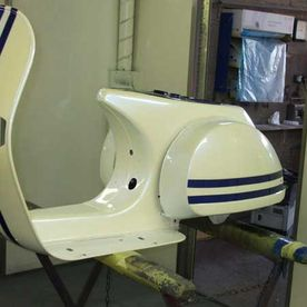 A scooters body getting painted